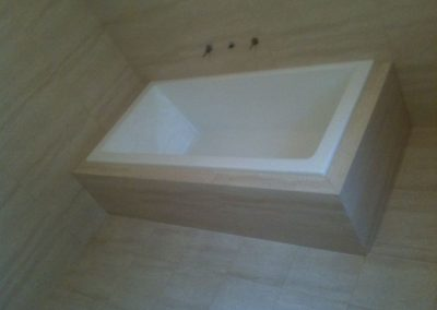 Installing this very stylish bathtub with floor to wall tiles