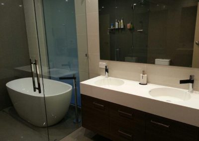 Installation of frameless showerscreen, free standing bath and upright tapware panels in Athelstone